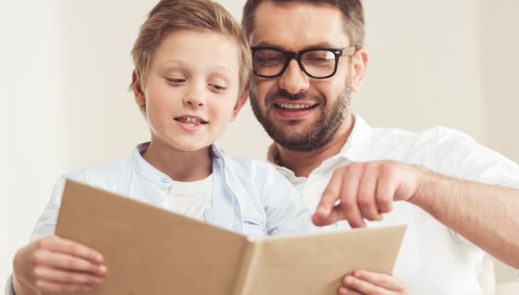 Far og sønn leser sammen hjemme